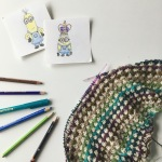 Two drawings of minions alongside a set of colour pencils and a colourful shawl
